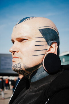 Close up of man with tattoos and earplug earring standing outdoors