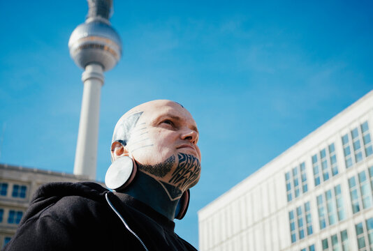 Low angle view of man with tattoos and earplug earring standing outdoors