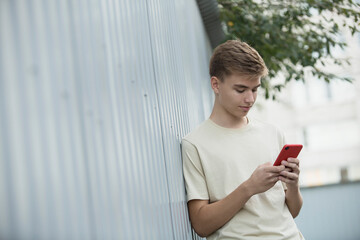 Tilt image of teenage boy using mobile phone while leaning on metallic wall