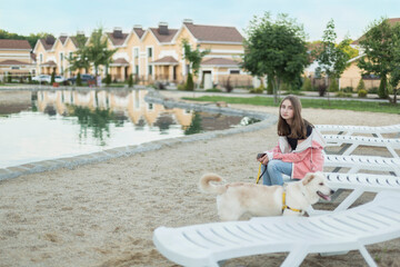Portrait of teenage girl sitting on deck chair by dog at beach