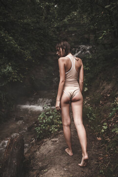 Rear view of woman in swimsuit walking on path by stream in forest