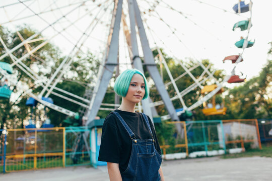 Portrait of teenage girl standing against ferris wheel at amusement park