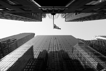 Directly below view of American Flag amidst skyscrapers against sky, New York City, New York, USA