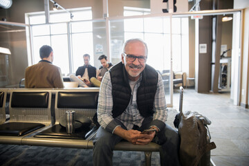 Portrait happy senior man with smart phone waiting in airport