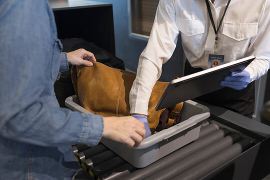 Airport security agent helping woman remove laptop at inspection