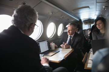 Business people with laptop working on private jet