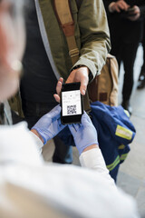Airport security agent checking passenger boarding pass on smart phone