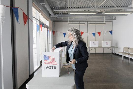 Female volunteer preparing voting booths in American polling place