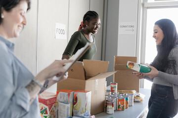 Female volunteers sorting food donations in community center