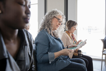 Woman reading brochure in conference audience Wall mural