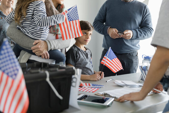 Boy holding American flag with his parents at polling place
