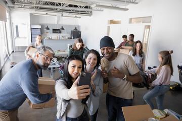 Happy volunteers taking selfie in community center