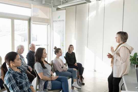 Female conference speaker talking to audience in community center