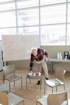 Senior man preparing for support group meeting in community center