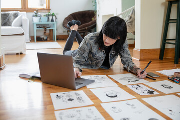 Young female transgender artist with laptop sketching on floor at home