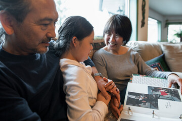 Happy Down Syndrome family looking at photo album on sofa