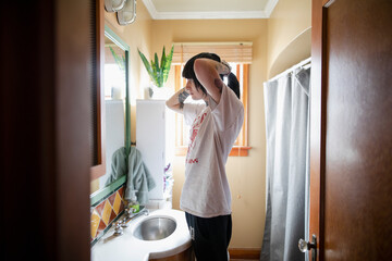 Young woman combing hair while looking in bathroom mirror