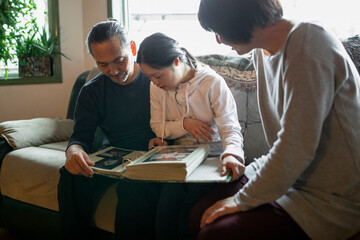 Down Syndrome family looking at photo album on sofa