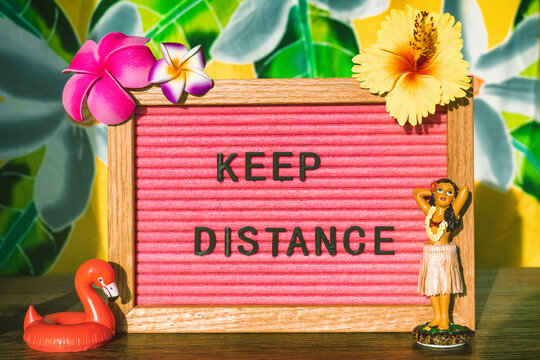 KEEP DISTANCE Covid-19 social distancing text sign for outdoor lifestyle people during summer. CORONAVIRUS concept. Tropical flowers felt board with hula dancer doll and pool float.