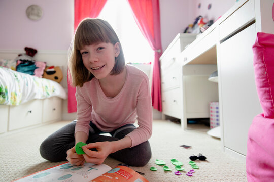 Girl sewing felt shape in bedroom