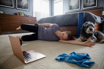Woman exercising in bedroom watching laptop