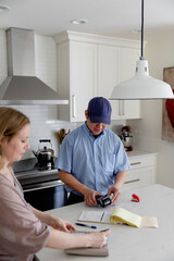 Woman paying workman by credit card in kitchen