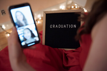 Close up teenage girl with graduation sign video chatting with friends