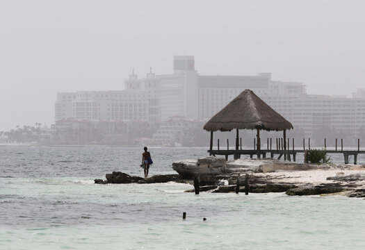 A tourist stands at a beach as dust carried by winds from the Sahara desert shrouds Cancun