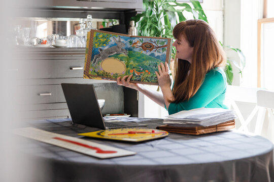 Female teacher with picture book teaching from home at laptop