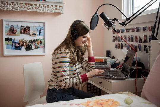 Teenage girl recording music on laptop in bedroom