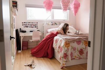 Teenage girl in red prom dress using smartphone in bedroom