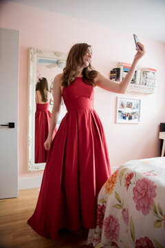 Happy teenage girl in red prom dress video chatting with smart phone