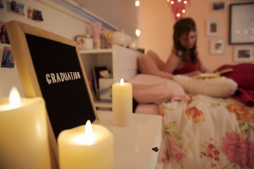 Teenage girl on bed next to graduation sign and candles in bedroom