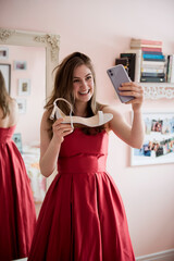 Happy teenage girl in prom dress showing shoes to friend on video chat