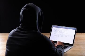 Caucasian man working on laptop on black background