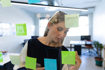 Caucasian woman writing on a sticky note