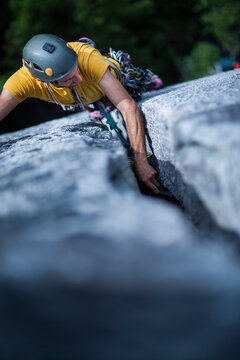 Man placing protection while lead rock climbing wide crack on granite