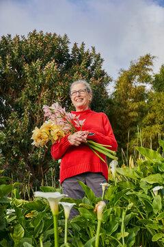 Retired Woman Holding Freshcut Flowers in her Garden