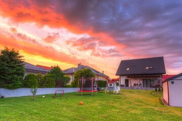 A modern single family house with a garden at sunset