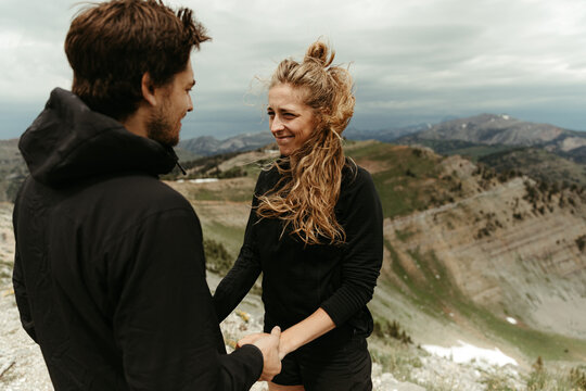 woman awkward but happy, smiles during a surprise mountain engagement