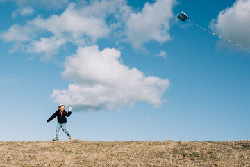 young boy flying a kite on the top of a hill on a beautiful day