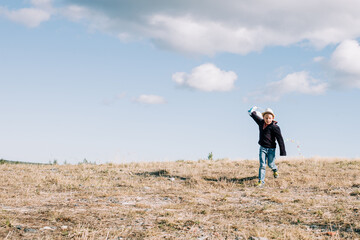young boy running with a kite at the top of a hill on a sunny day