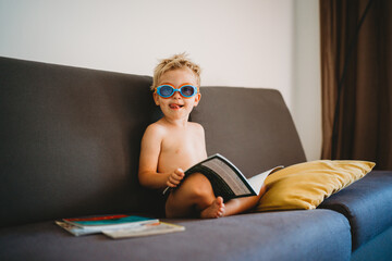 Male child reading topless with goggles and sticking his tongue out