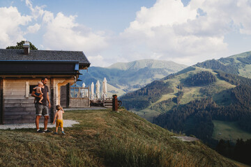 Father and children walking in mountains with stunning views in summer