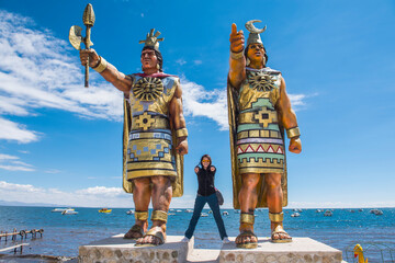 Poster Historisch geb. Woman posing at statues of Sun God and Moon Goddess, Lake Titicaca