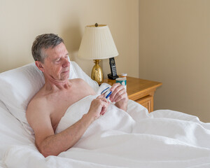 Senior retired caucasian man lying in adjustable bed on incline. He is checking his blood oxygen...