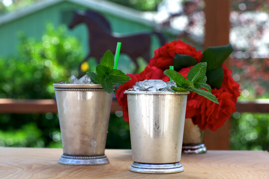 Mint julep drinks in silver cups with red roses and horse silhouette in background