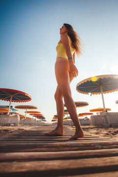 young slim beautiful woman, sexy model by the sea on the beach, playful, dancing, running, indie style, summer vacation, sunny, having fun, positive mood, romantic, happy