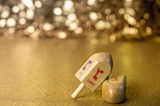 Dreidel game on a gold glitter and sequin background that sparkles and has lots of copy space