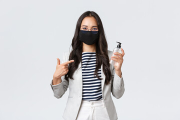 Business, finance and employment, covid-19 preventing virus and social distancing concept. Smiling cute asian office worker in face mask recommend using hand sanitizer while at work